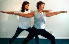Nancy Rakela, LAc, OMD demonstrating a yoga posture with friend